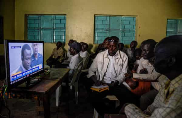 People watch the start of the ICC trial of Dominic Ongwen in Lukodi, Uganda on December 6, 2016.