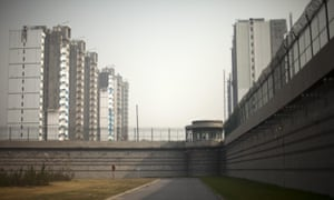 A paramilitary policeman guards a tower on the barb-wired wall of the Number One Detention Centre in Beijing.