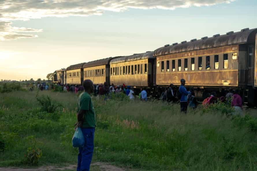Commuters wait to board a train