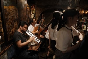 Musicians entertain customers in a tiny bar
