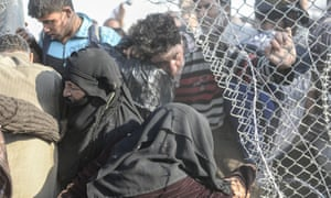 Syrians fleeing the war pass through border fences into Turkey.
