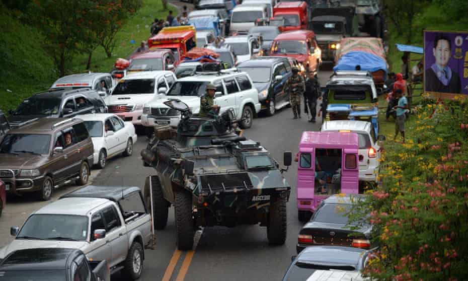 An armoured personnel carrier moves past gridlocked vehicles of residents fleeing Marawi.