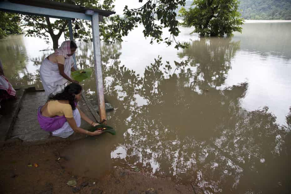 Villagers offer prayers for the floodwaters to recede, in Chandrapur village east of Gauhati, Assam state, India.