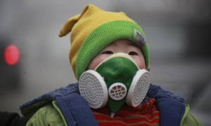 A young boy wearing a dust respirator walks in heavy smog in Jinan, China