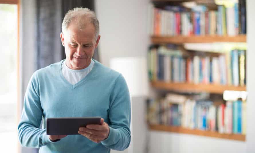Senior man using tablet computer at home