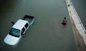 A driver walks past an abandoned truck while checking the depth of an underpass during the aftermath of Hurricane Harvey in Houston, Texas, on 28 August 2017.