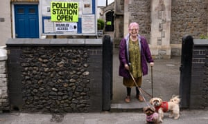 A woman stands with her dogs after placing her vote in local elections in Broadstairs, Kent.