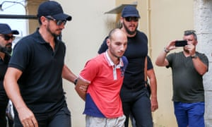 Yiannis Paraskakis is escorted by police on Crete.