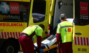 Health workers unload a stretcher with a patient from an ambulance in the emergency unit at a hospital in Madrid.