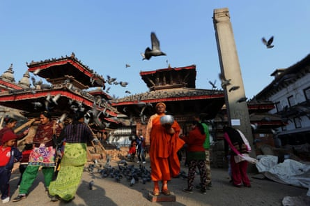 A Buddhist monk waits for alms in Durbar Square, a UNESCO heritage site in Kathmandu, capital of Nepal