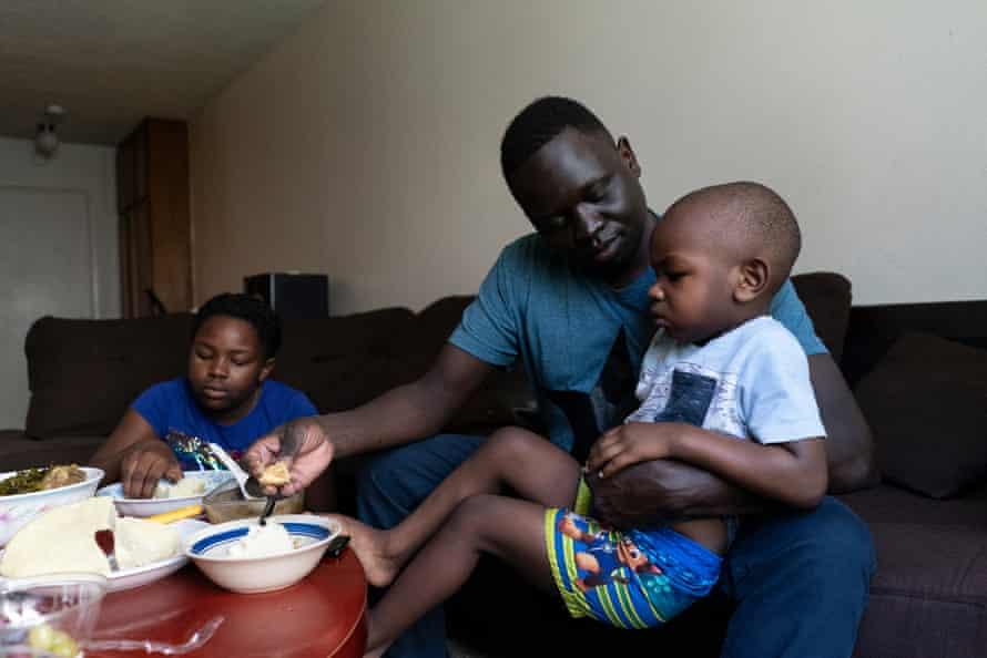 Okello feeds his son Ezekiel dinner at his apartment.