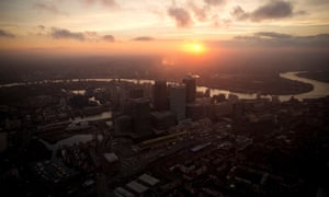 Sun sets over Canary Wharf and the City of London.