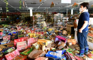 Kurashiki, Japan. A member of staff inspects the damaged caused by floodwaters at a supermarket in the Mabicho area