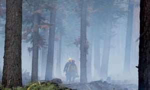 Fire crews work on the Emerald fire along California Highway 89, one of three wind-whipped wildfires burning along the Sierra Nevada.