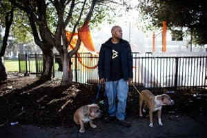 Eric Clark with his dogs. Behind him are the tents of other homeless people in West Oakland.