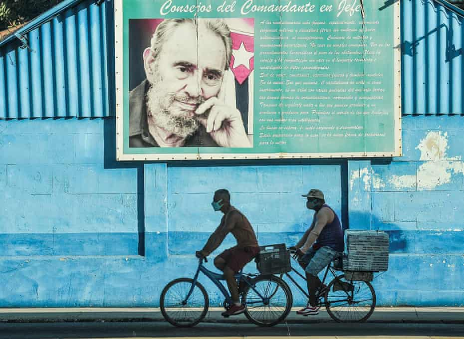 Men ride their bicycles next to a poster of the late Cuban leader Fidel Castro in Havana this week.