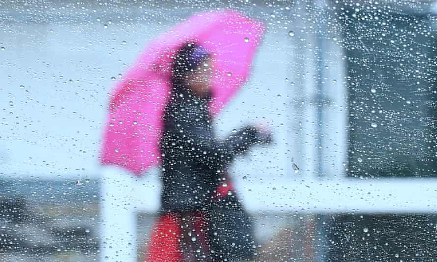 Raindrops are seen on a vehicle's window as a woman walks by using an umbrella.