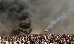 Palestinians look at smoke billowing from burning tyres during clashes with Israeli forces near the border between the Gaza strip and Israel