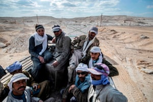 Group of men sitting in the back of a truck