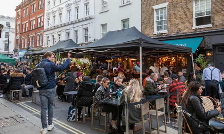 People dine outside restaurants and pubs in Soho, London, in April.