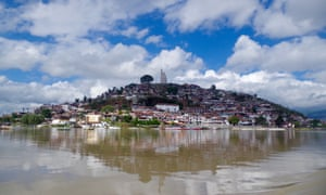 Daytime shot, with blue skies and light cloud, of Janitzio island, with José Morelos statue at its peak, Pátzcuaro, Mexico
