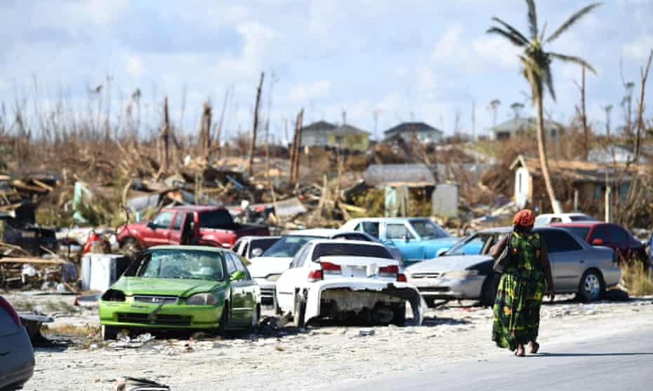 A woman walks by destroyed cars in the Mudd neighborhood in Marsh Harbour, Great Abaco, on 7 September 2019, in the aftermath of Hurricane Dorian.