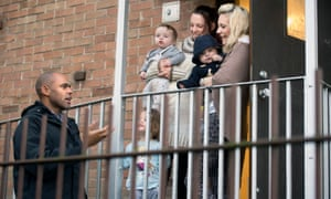 Rees talks to mothers outside the laundry room of a block of flats.