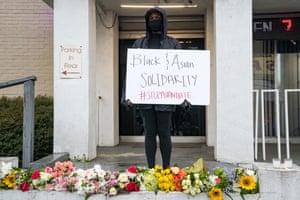 عزادار با علامت در یکی از مکانهای تیراندازی در آتلانتا ، جورجیا ایستاده است.