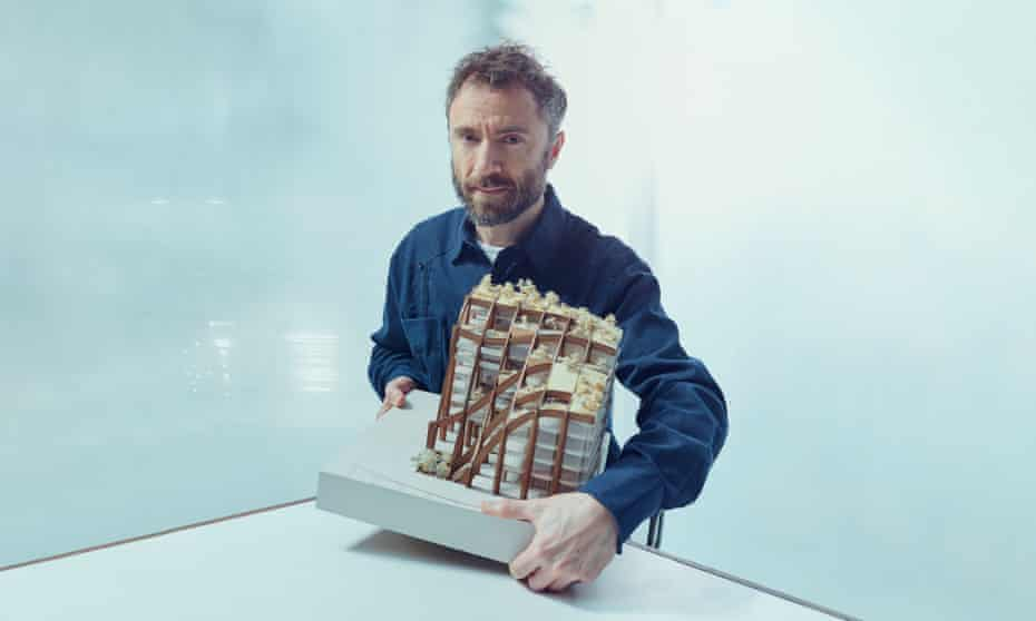 Thomas Heatherwick holding a model of a building