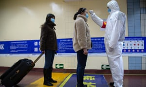 A health worker checks the temperature of a traveller