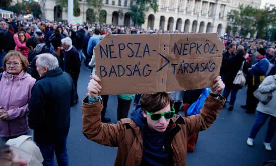 A demonstrator holds a placard reading 'Népszabadság, People's Republic'