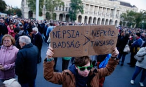 A demonstrator holds a placard reading, 'Nepszabadsag, People's Republic' as crowds gather in front of the Parliament building in Budapest to show their support of the Hungarian political daily