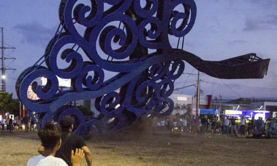Protesters haul down a 'Tree of Life' sculpture in Managua, Nicaragua