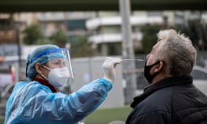 A healthcare worker takes a swab from a man for a rapid antigen test at a drive-through testing site in Athens, Greece.