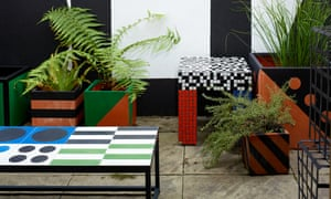 A patchwork of different colours and shapes on big square plant pots and a table in the garden.