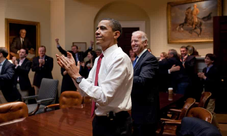 President Barack Obama, Vice President Joe Biden, and senior staff applaud in the Roosevelt Room of the White House, as the House passes the health care reform bill