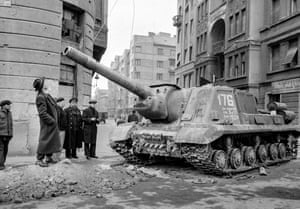 Passersby look up at a disabled Soviet tank after the first Soviet departure. People wandered the streets, finding it hard to believe they had driven the enemy away