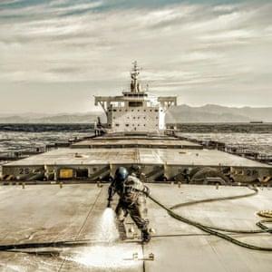 Crew member cleans deck