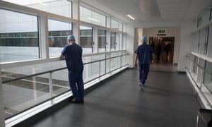 Operating theatre staff walk along a corridor in Birmingham Queen Elizabeth Hospital.
