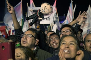 Supporters hold aloft a López Obrador doll