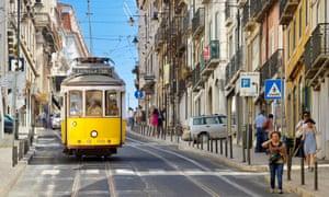 People walk down a street in Lisbon