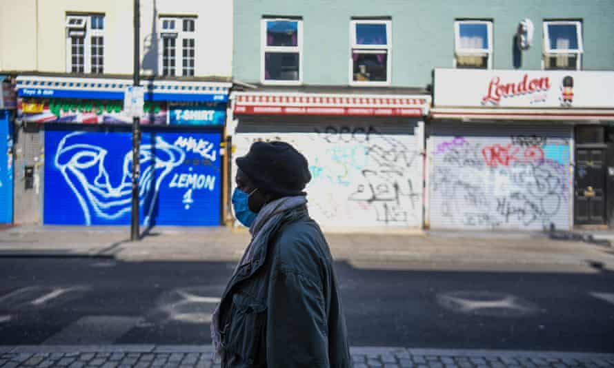 A woman wearing a mask walks down an empty Camden High Street, London, as the UK continues in lockdown to help curb the spread of the coronavirus