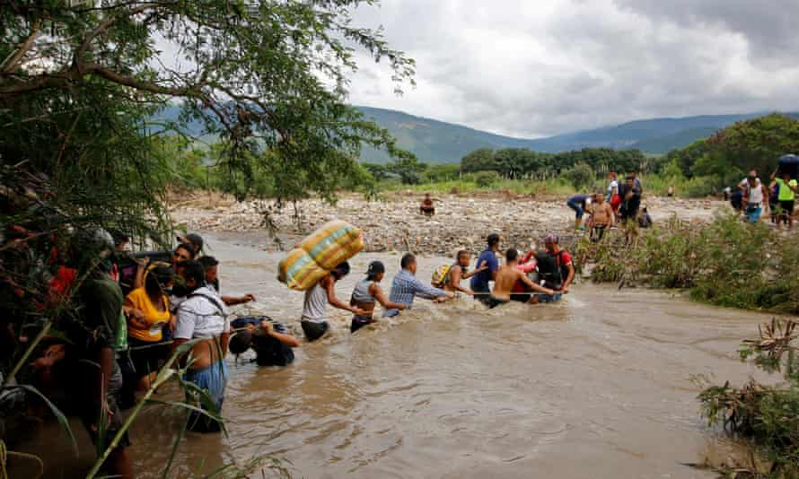 Line of migrants use a rope to cross waist-deep border river