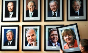 A portrait of the German chancellor Angela Merkel is added to a wall featuring pictures of her predecessors