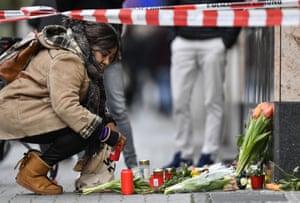 A woman sets a candle near the scene where several people were killed in Hanau, Germany, 20 February