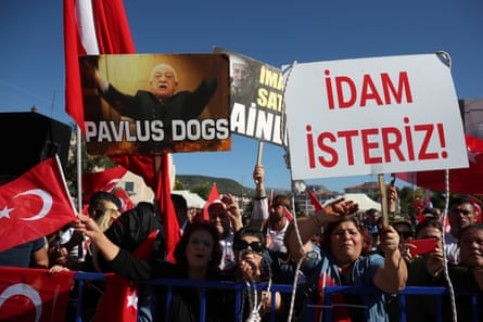 Supporters of President Erdoğan wave Turkish flags during the trial. The placard reads: 'We want execution!'.