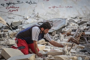 Aljaleel rescues a cat from the rubble of a bombed area of Khan Sheikhun as he searches for surviving felines to take to his sanctuary