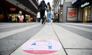 a sticker on a pavement in stockholm tells people to keep social distancing