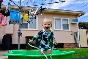 A toddler cools off by playing with a garden hose in a Sydney backyard.