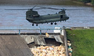 RAF Chinook helicopter prepares to drop sand bags to shore up stricken Toddbrook Reservoir.